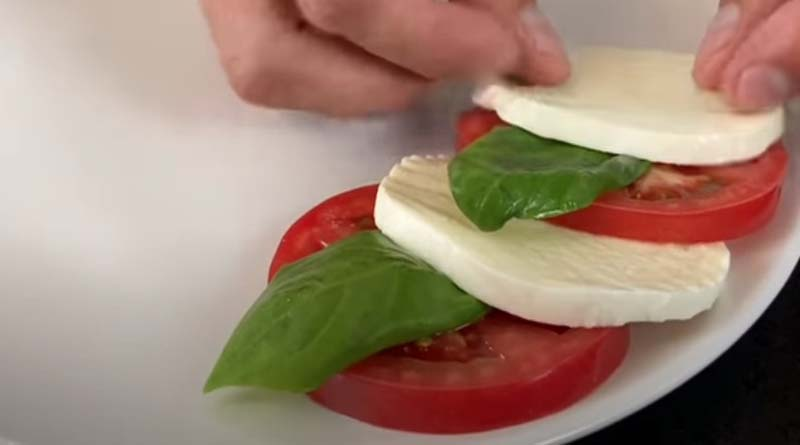Базилик, сыр и томаты на тарелке